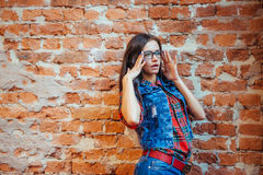 Beautiful young woman stands near the old brick wall. Youth styl Stock Photo