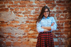 Beautiful young woman stands near the old brick wall. Youth styl Royalty Free Stock Image