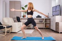 Beautiful young woman staying in Warrior II yoga pose stock photo