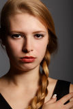Beautiful young woman with stern look and plait hairstyle Royalty Free Stock Image