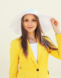 Beautiful young woman in the straw hat and yellow suit Stock Images
