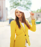 Beautiful young woman in the straw hat and yellow suit outdoors Stock Photography