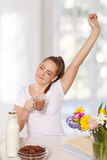 Beautiful young woman streching herself while holding a glass of. Hot drink Stock Image
