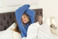 Beautiful young woman stretching in bed and smiling at home. Winter atmosphere royalty free stock photo