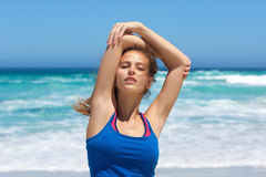 Beautiful young woman stretching exercise at the beach Stock Photos