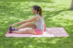 Beautiful young woman stretching outdoors Royalty Free Stock Photo
