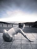 Beautiful young woman stretching at the sea stock image