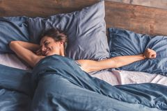 Young woman in bed. Beautiful young woman is stretching and smiling while lying in bed in the morning Stock Images