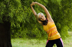 Beautiful young woman stretching stock images