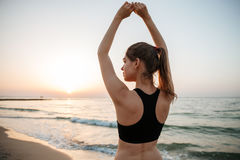 Beautiful young woman stretching during yoga on the beach Royalty Free Stock Images