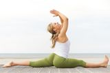 Beautiful young woman stretching yoga pose at beach Stock Photography