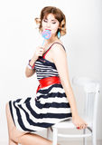 Beautiful young woman in a striped dress eats a lollipop Royalty Free Stock Photography