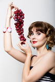 Beautiful young woman in a striped dress holding a bunch of grapes Royalty Free Stock Image