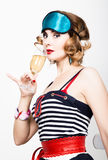Beautiful young woman in a striped dress holding a glass of champagne Royalty Free Stock Images