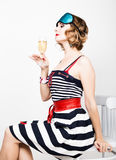 Beautiful young woman in a striped dress holding a glass of champagne Stock Photography