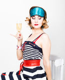 Beautiful young woman in a striped dress holding a glass of champagne Stock Photos