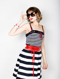 Beautiful young woman in a striped dress holding over size sunglasses Stock Image