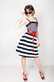 Beautiful young woman in a striped dress holding over size sunglasses Royalty Free Stock Image