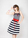 Beautiful young woman in a striped dress holding over size sunglasses. Beautiful young woman in a striped dress holding a glass of champagne Stock Photography