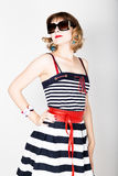 Beautiful young woman in a striped dress holding over size sunglasses Royalty Free Stock Photo