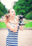 Beautiful young woman in striped dress with old retro camera Royalty Free Stock Photos
