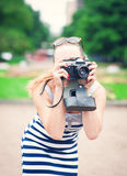 Beautiful young woman in striped dress with old retro camera Stock Photo