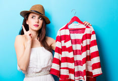Beautiful young woman with striped jacket on hanger standing in Stock Image
