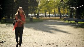 Beautiful Young Woman Student with a Backpack While Walking in Autumn Park, Flying Birds on Background