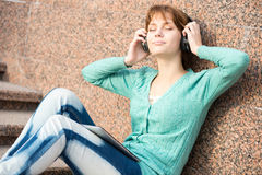 Beautiful young woman student with headphones. Outdoor music girl Stock Photo