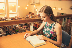 Beautiful young woman student in library. Beautiful young woman in libraryreading book behind the table Stock Image