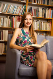 Beautiful young woman student in library Royalty Free Stock Images