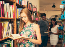 Beautiful young woman student in library Stock Photo