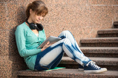 Beautiful young woman student with note pad and headphones. Outdoor student. Royalty Free Stock Images