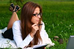 Beautiful young woman studing in park Stock Photo