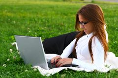 Beautiful young woman studing in park Royalty Free Stock Photography