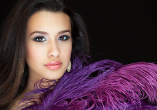 Beautiful Young Woman. Studio portrait with a purple feather on a black background Stock Photography