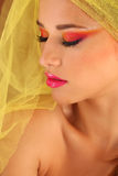 Beautiful young woman in the studio, wearing colorful make up Royalty Free Stock Image