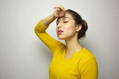 Beautiful young woman suffer with close eyes from migraine headache with gray background. Beautiful young woman suffer with close eyes from migraine headache Stock Image