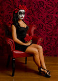 Beautiful young woman with sugar skull surounded by red Royalty Free Stock Photography