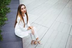 Beautiful young woman in suit is sitting in a backyard of office building. Young attractive businesswoman with long hair and beautiful make-up, wearing white Royalty Free Stock Images