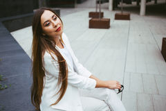 Beautiful young woman in suit is sitting in a backyard of office building. Stylish female with red lipstick is resting at outdoor square between work break Royalty Free Stock Photos