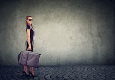 Beautiful young woman with suitcase ready to explore city royalty free stock photo