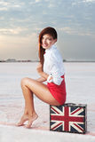 Beautiful young woman with suitcase with British flag outdoor Royalty Free Stock Photo