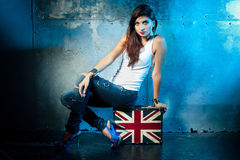 Beautiful young woman with suitcase with British flag. Portrait of casual young woman with suitcase with British flag, metal wall as a background Royalty Free Stock Image