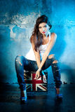 Beautiful young woman with suitcase with British flag. Portrait of casual young woman with suitcase with British flag, metal wall as a background Stock Photography
