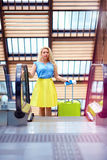 Beautiful young woman with suitcase moving on escalator in airport terminal Royalty Free Stock Image