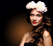 Beautiful Young Woman with Summer Pink Flowers. Long Permed Curly Hair and Fashion Makeup. Beauty Girl with Flowers Royalty Free Stock Image