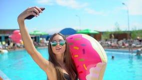 Beautiful young woman in summer taking selfies on smartphone. Bikini girl relaxing in tropical swimming pool. The stock video