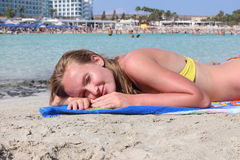Beautiful young woman sunbathing on the beach. Stock Photos