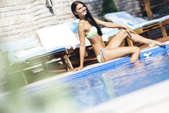 Beautiful young woman sunbathing at the poolside Stock Images